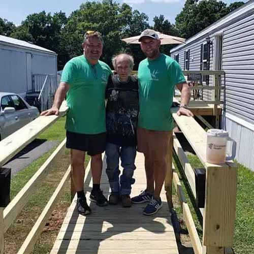 Elderly man between two 516 project volunteers on the new ramp to his home -516 Project of Fredericksburg Virginia