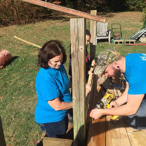 Man and woman installing a deck rail volunteering for 516 Project of Fredericksburg Virginia
