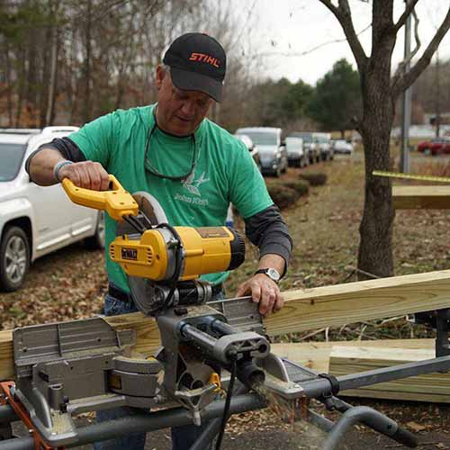 Man cutting deck rail post with compound miter saw volunteering for 516 Project of Fredericksburg Virginia